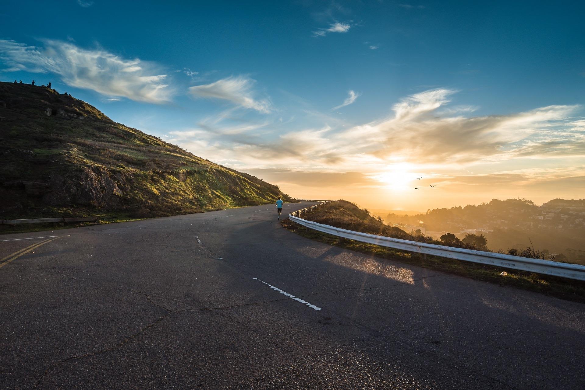 Eine person läuft auf einer Straße einen Berg hinauf. Die Sonne scheint im Hintergrund.