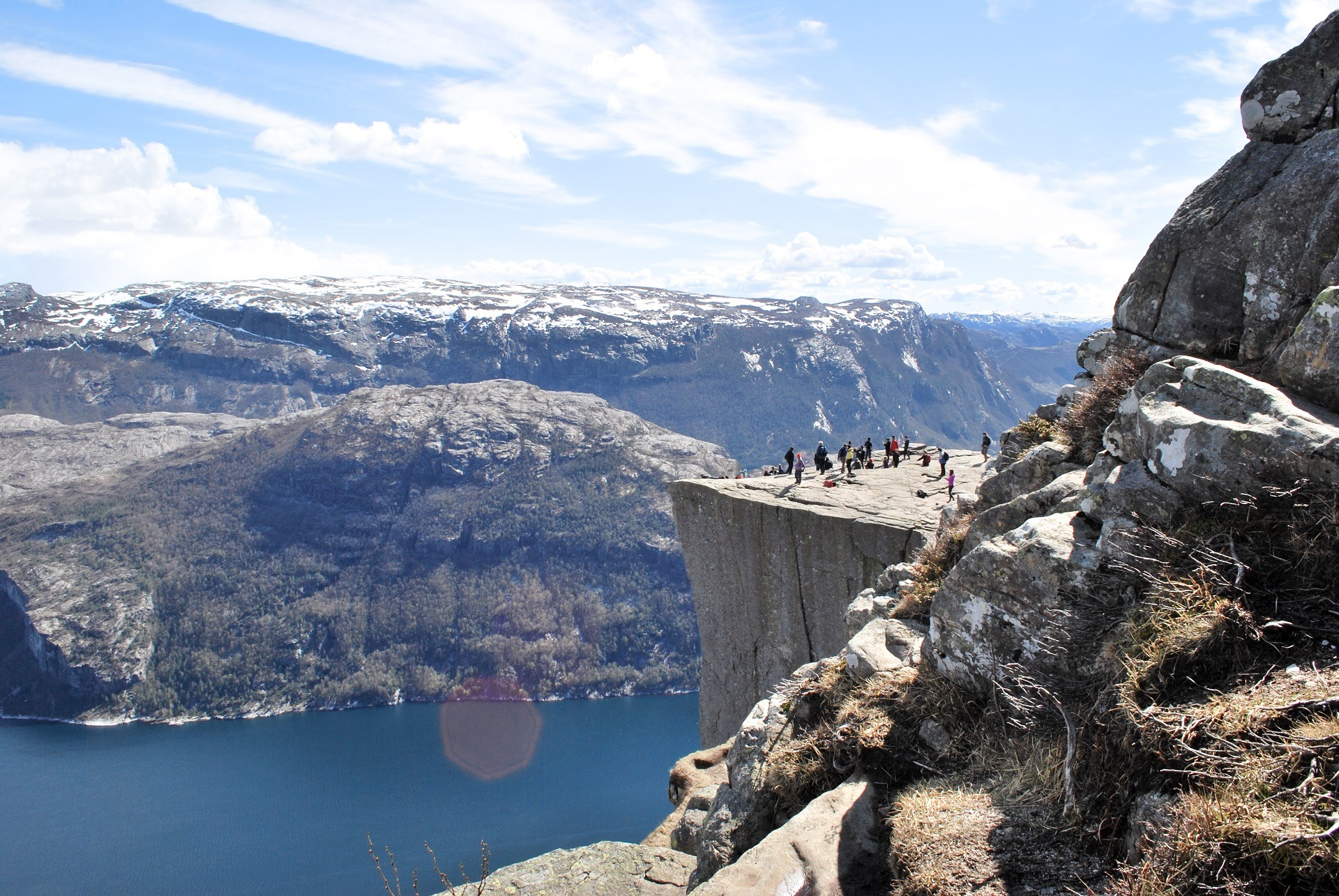 Eine Gruppe von Bergesteigern steht auf einem Plateau. Im Tal ist ein See zu sehen.