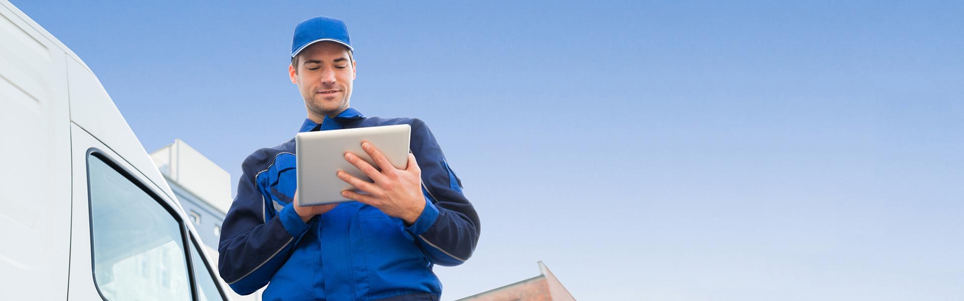 Ein Aussedienstmitarbeiter steht vor seinem Transporter und tippt auf seinem Tablet.
